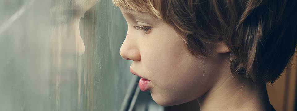 A young boy looking out a window
