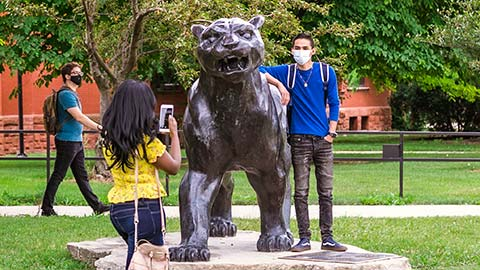 A student poses with the Pounce Panther statue as a friend takes his photo