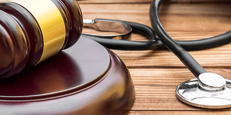 Gavel with stethoscope and books on the table.