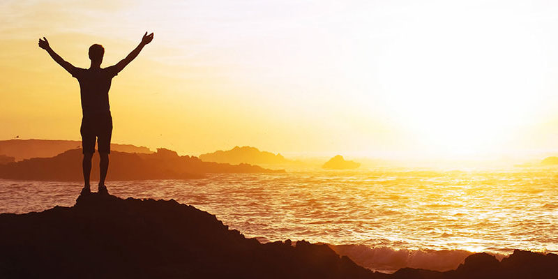 Silhouette of a man holding his arms in the air while watching a sunset over the ocean
