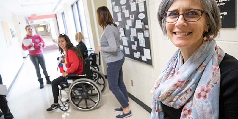 Professor with students working on assistive technology and universal access