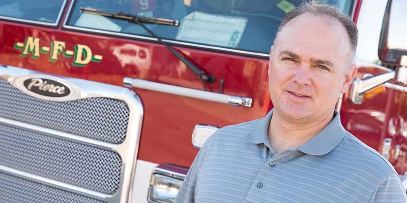 Portrait of a man standing in front of a firetruck