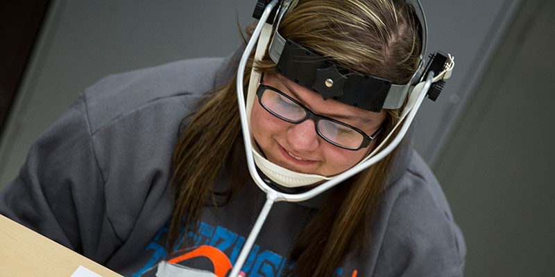 Student wearing an assistive device for writing
