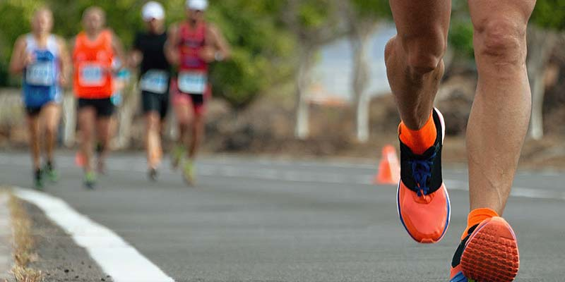 Close up of a person running with people running behind them in a race setting