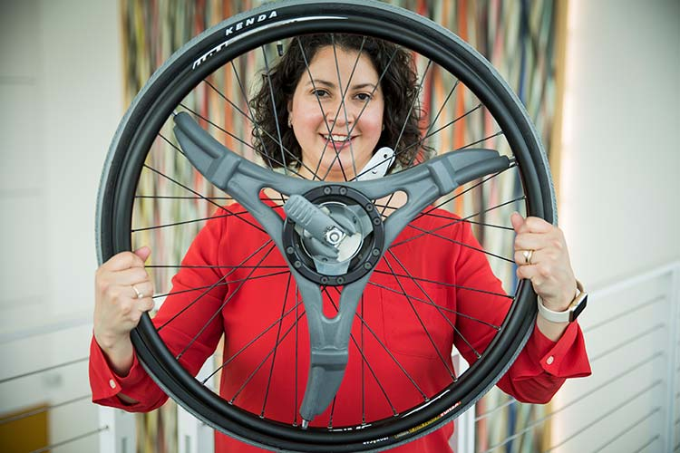 Brook Slavens, associate professor, showcases a wheelchair wheel that features a multigeared system that operates much like the gears on a bicycle.