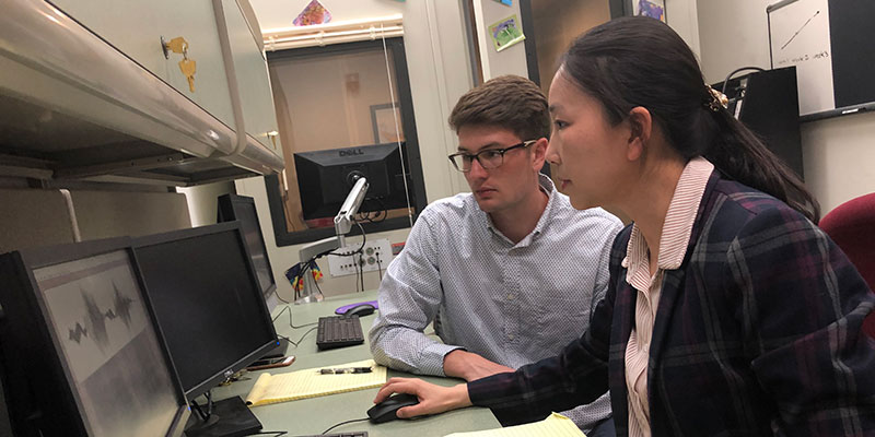 Professor Yang with a student in the Speech Acoustics & Development Lab