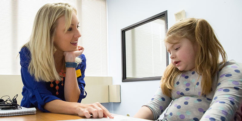 Student working with a young girl on speech