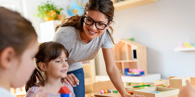 Woman working with young children playing with blocks
