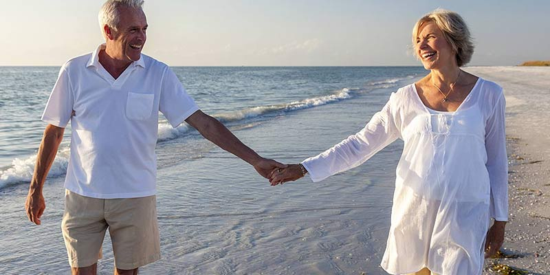 Man and woman holding hands walking on the beach