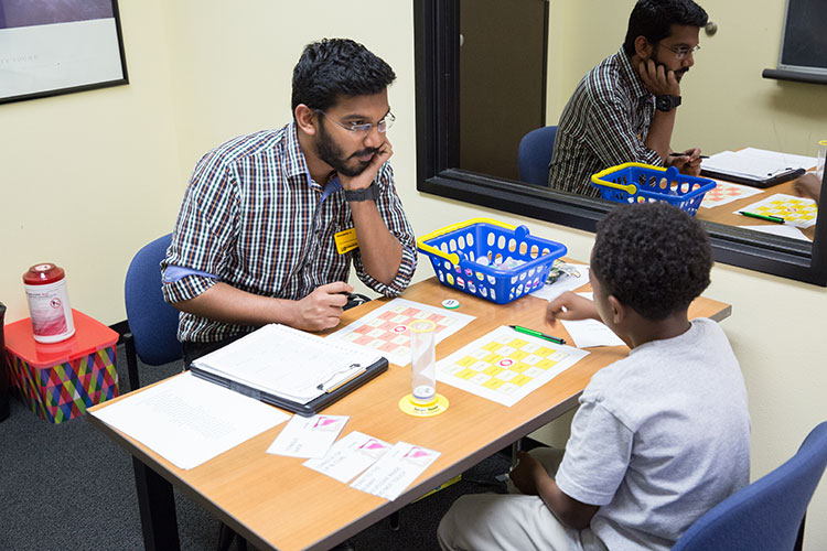 Student working with a child on speech