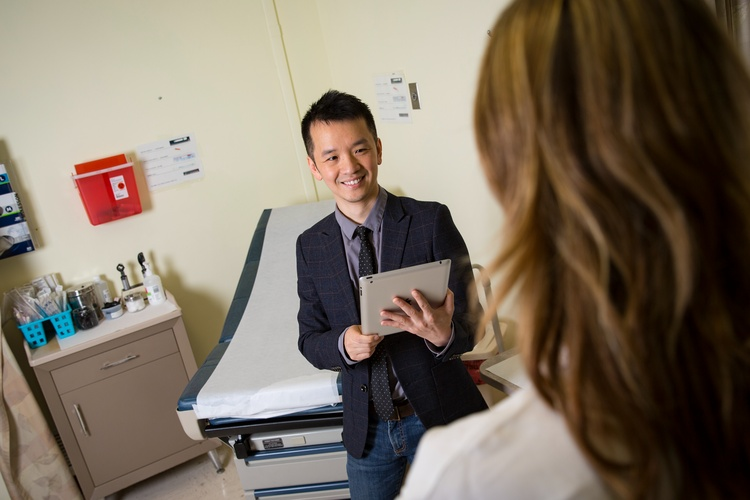 Jake Luo stands with a tablet in a doctor's office talking with a doctor about Center for Health Systems Solutions.