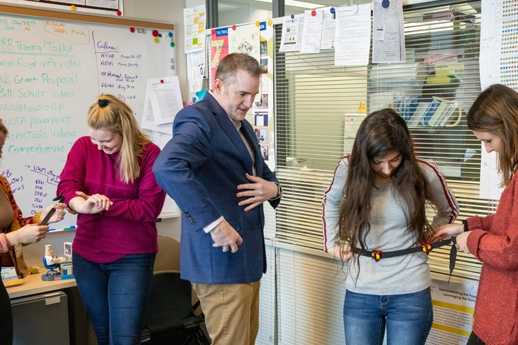 Dean and Professor Timothy Behrens showing a student how to use a pedometer.