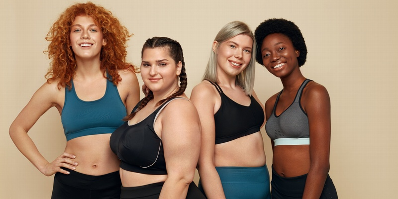Four body positive women standing together.