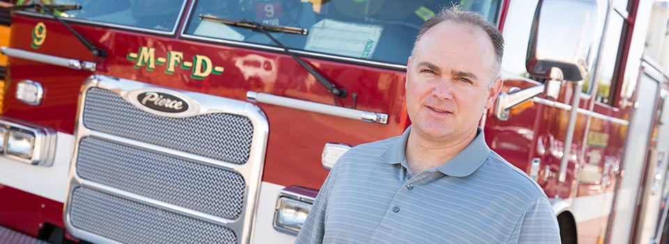 Kyle Ebersole, director of the Human Performance & Sport Physiology Laboratory stands in front of a Milwaukee Fire Department truck