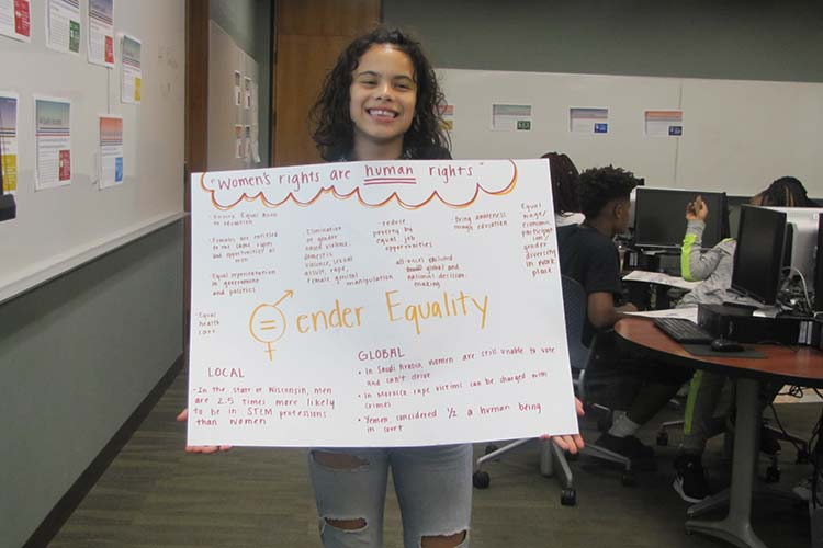 A smiling student holding a poster about gender equality