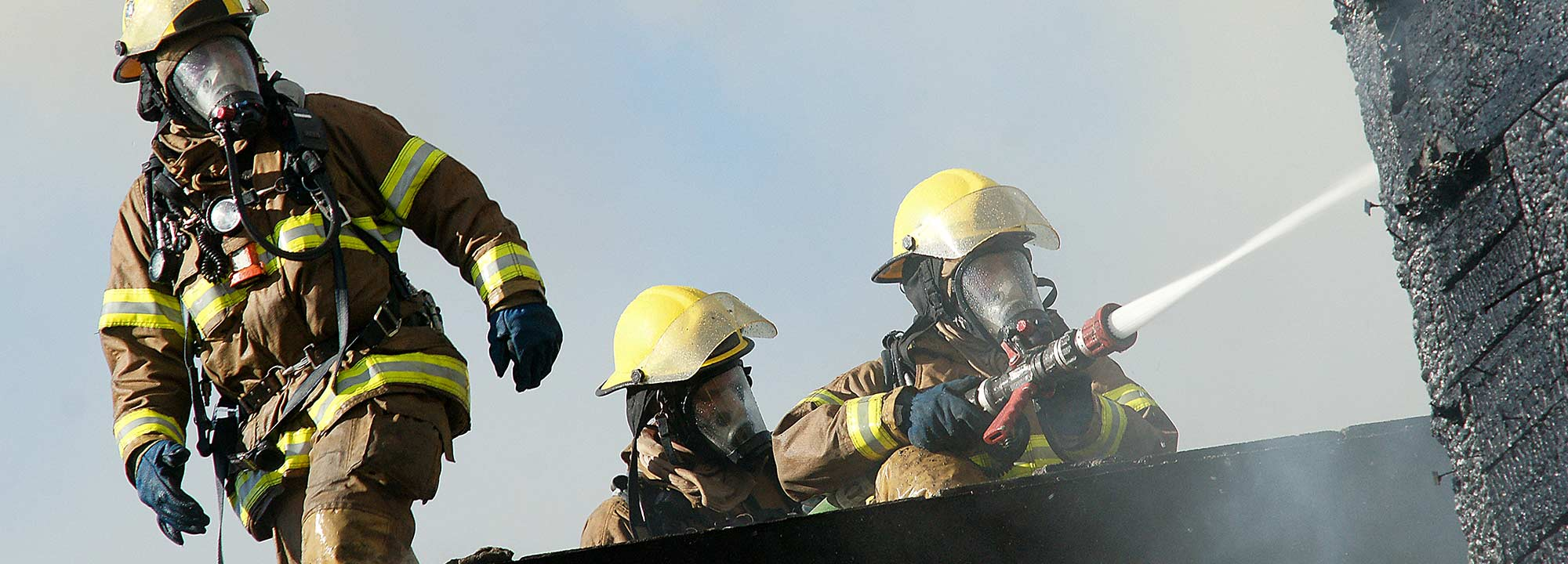 Three firefighters hose down a fire