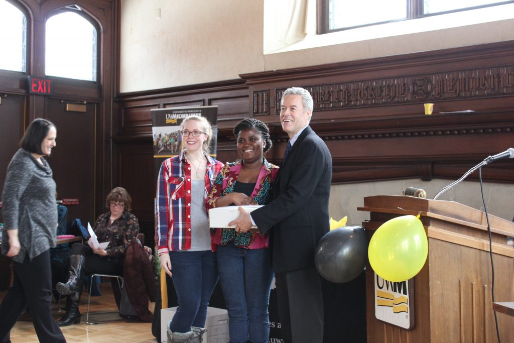 Loretta Mulberry amd Ewurama Okine stand at the front of Greene Hall with UWM Chancellor Mark Mone who holds a gift box containing one of their prizes.