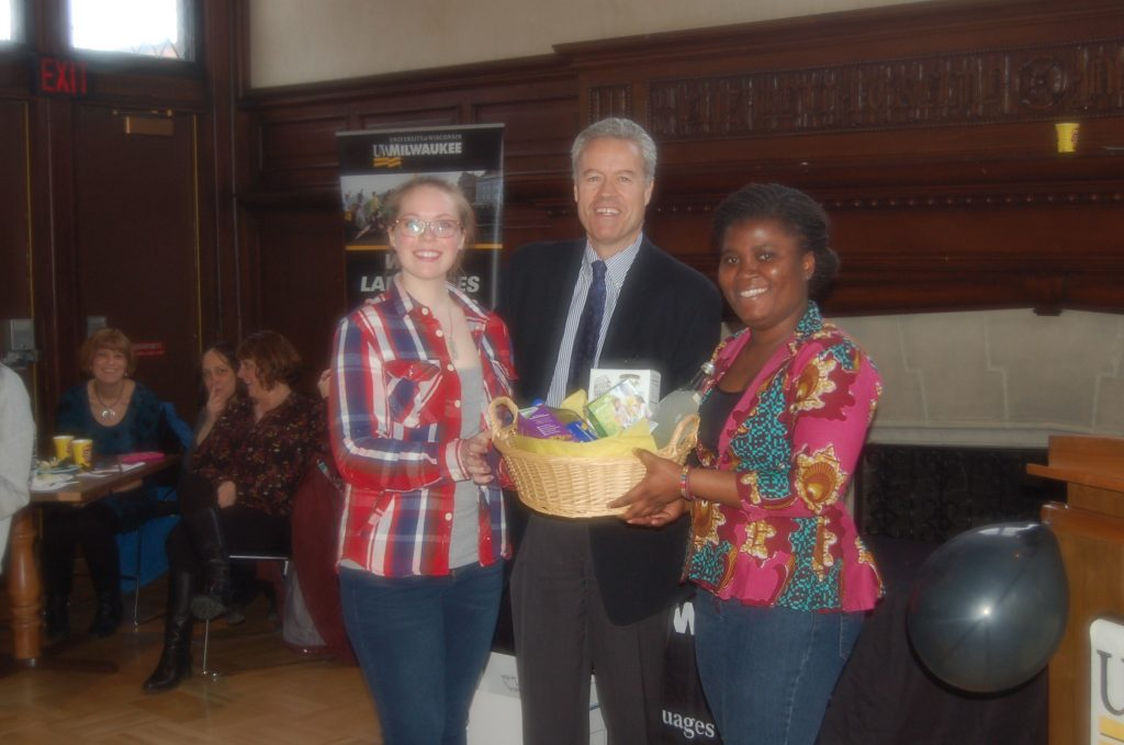 Loretta Mulbery, Chancellor Mone, and Ewurama Okine stand at the front of Greene Hall. Mulberry and Okine hold up a large basket with cookies and beverages, a prize they have just been awarded.