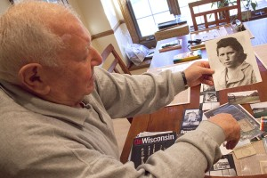 Holocaust survivor Nate Taffel holds a photograph of his youngest sister, Faiga, who drowned in a river in Poland, during an interview with UWM Journalism, Advertising, and Media Studies students.