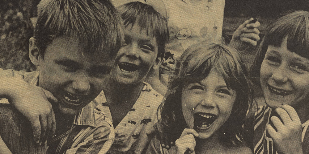 Black and white photograph of children laughing from the cover of vol. 2, no. 25 of Kaleidoscope