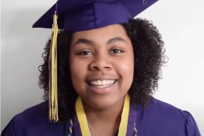 A high school graduate smiles while wearing a cap and gown.