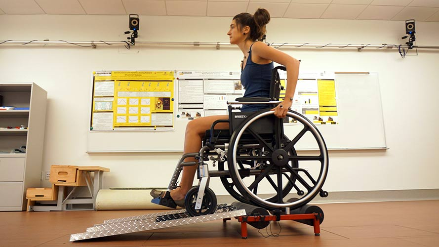 Young woman in a wheelchair that is sitting on Mclain Wheelchair Training Rollers