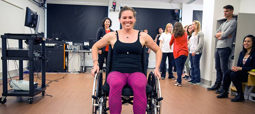 Associate Professor, Brooke Slavens, teaches a class on muscle activity assessment to investigate the biomechanics of manual wheelchair mobility using motion capture and reflective markers on the human subject, with a geared wheel system.