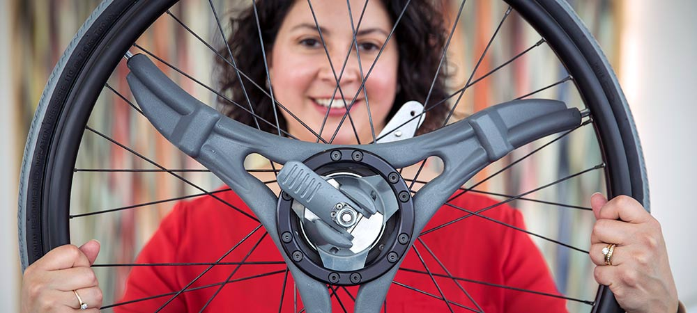 Lab director, Brooke Slavens, holds a multi-geared wheel system for a wheelchair that operates much like the gears on a bike.