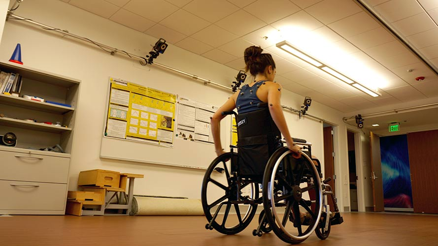 Young woman in wheelchair with reflective markers on her shoulders and arms with the Vicon Nexus Camera System overhead