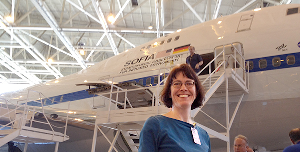 Jean Creighton in the hangar with the SOFIA aircraft.