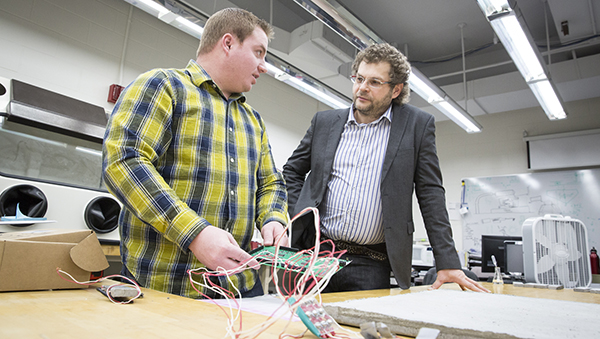 "Konstantin Sobolev (right) and doctoral student Scott Muzenski get ready to attach wiring to a test sample of a ""smart"" concrete composite they developed that has a life span of more than 120 years. (Photo by Troye Fox)"