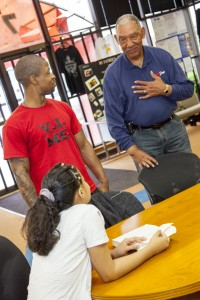 Albert Holmes, CEO of My Father's House, chats with Dontae Dickerson and his daughter, Diamond. (UWM Photo/Pete Amland)