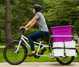 """Student compost and gardens supervisor and UWM senior Renee Frederick users a cargo bike, nicknamed """"Betty the Biocycle,"""" to tote coffee grinds to the hoop house for composting."""