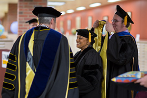 Rodney Swain, dean of the College of Letters & Science, prepares to place a hood on former French Minister of Justice Christiane Taubira during a Saturday ceremony at the University of Wisconsin-Milwaukee, where she received an honorary doctorate of laws and human rights. (UWM Photo/Elora Hennessey)