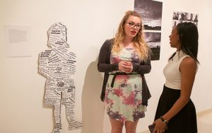 Ashley Matter (left) discusses the collage of headlines, quotes and labels about black Americans that she and collaborator Nicole Beilke (not pictured) created.
