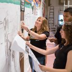 Undergraduate students work on a mural that tells the story of the  United Migrant Opportunity Services (UMOS), one of Wisconsin's leading advocacy organizations for people who lack adequate employment opportunities and social services. (UWM Photo/Elora Hennessey)