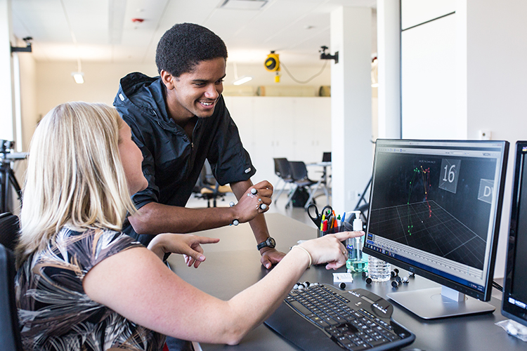 Freshman Joseph Rausch (right) works with Alyssa Schnorenberg in professor Brooke Slavens' lab at UWM's Innovation Campus. Rausch is helping Slavens study the motion of the shoulder before and after rotator cuff surgery. (UWM Photo/Elora Hennessey)
