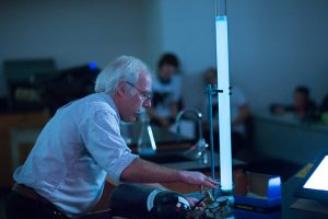 Chuck Wimpee, associate professor of biological sciences, displays the results when he pumps oxygen into a tube of water with bioluminescent bacteria in it during a session at the Wisconsin Science Festival. (UWM Photo/Elora Hennessey)
