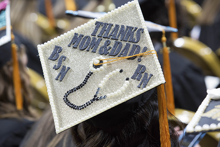 A new graduate uses the mortarboard to pass along a message to parents. (UWM Photo/Troye Fox)