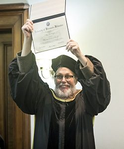 Chris Kegel holds his honorary doctor of business degree aloft. (UWM Photo/Derek Rickert)