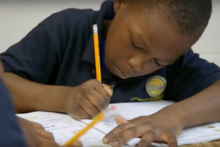 A young boy writes with a pencil in his grade school classroom.