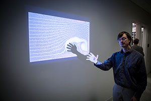 Tom Hansen demonstrates computational fluid dynamics software he developed to show the interactions of users with the flow fields.