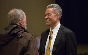 Chancellor Mark Mone chats with Mark Schwartz, distinguished professor of geography, before beginning his spring plenary address at the Helene Zelazo Center for the Performing Arts. (UWM Photo/Troye Fox)