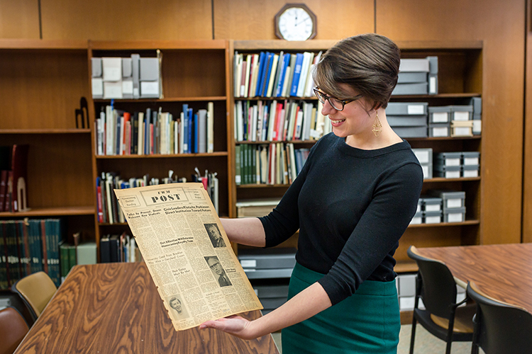 Abigail Nye, interim head of the UWM Archives, takes a look at the first edition of the UWM Post student newspaper, published Sept. 26, 1956. (UWM Photo/Elora Hennessey)