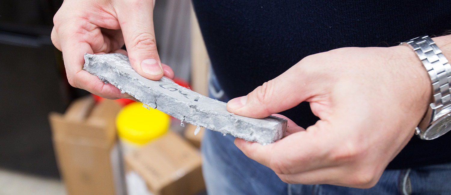 A piece of concrete bends in a man's hands.