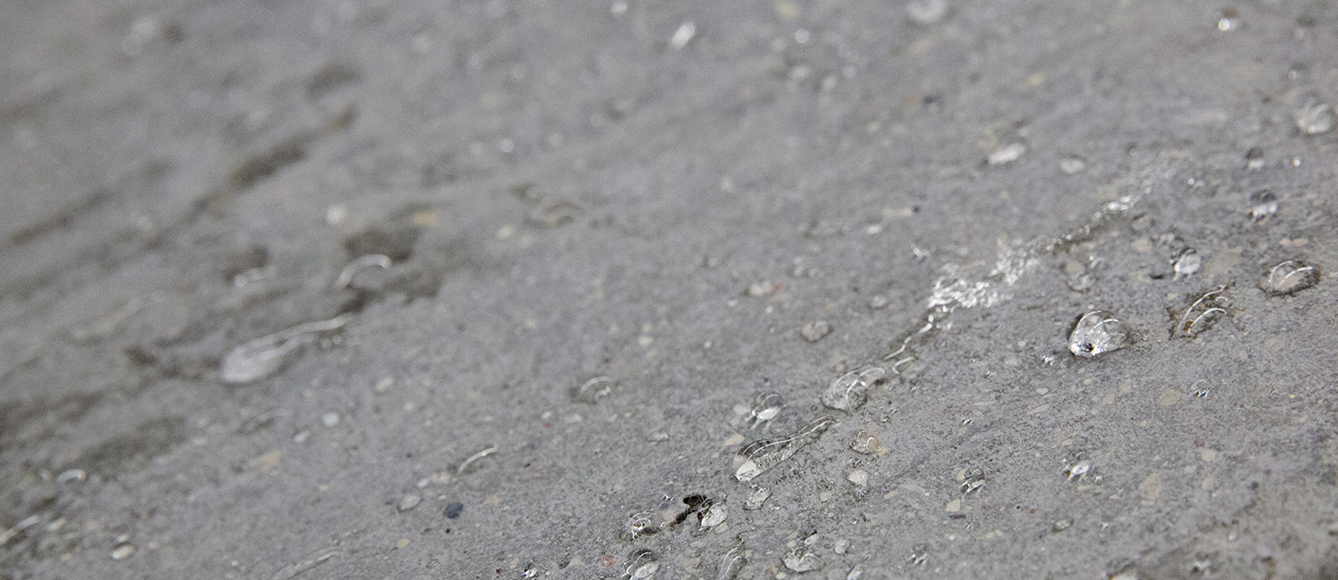 Water beads on concrete.