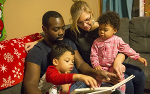 Amber and Jared Anderson read to their children, Wesley, 4, and Bay, 1. Family time competes with schoolwork time for the Andersons, both UWM seniors studying to be science teachers. (UWM Photo/ Derek Rickert)