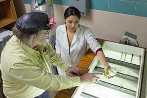 Cristal Sanchez-Estrada checks out algae samples in a lab at the School of Freshwater Sciences Lab with her mentor Russell Cuhel, a senior scientist in the school. (UWM Photo/Troye Fox)