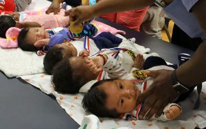 Nurses tend to babies lined up on a table.