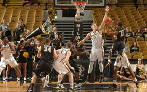 JJ Panoske blocks a shot while playing basketball for UWM